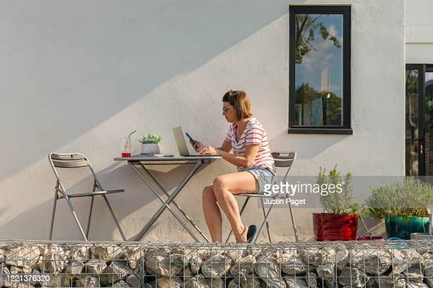 woman working from home garden - laptop stock pictures, royalty-free photos & images