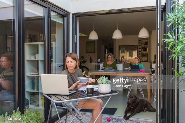 woman working from home. her family are eating lunch in the background - lunch stock pictures, royalty-free photos & images