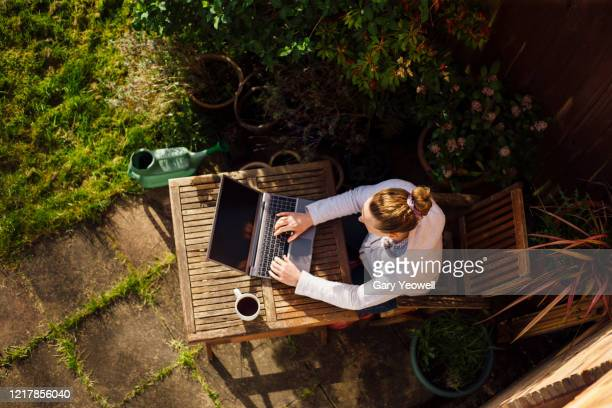 woman working from home in her garden - using laptop stock pictures, royalty-free photos & images