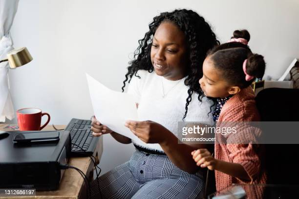 """woman working from home in small space with child around. - """"martine doucet"""" or martinedoucet stock pictures, royalty-free photos & images"""