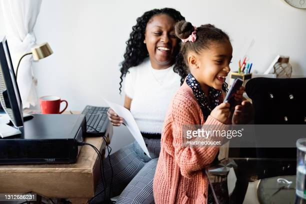 """woman working from home in small space with child trying to steal mobile phone. - """"martine doucet"""" or martinedoucet stock pictures, royalty-free photos & images"""