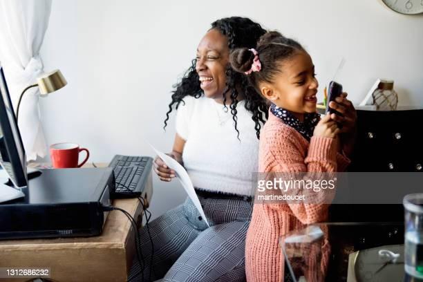 """携帯電話を盗もうとする子供と小さなスペースで自宅で働く女性。 - """"martine doucet"""" or martinedoucet ストックフォトと画像"""
