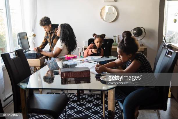 """woman working from home in small space with children around. - """"martine doucet"""" or martinedoucet stock pictures, royalty-free photos & images"""