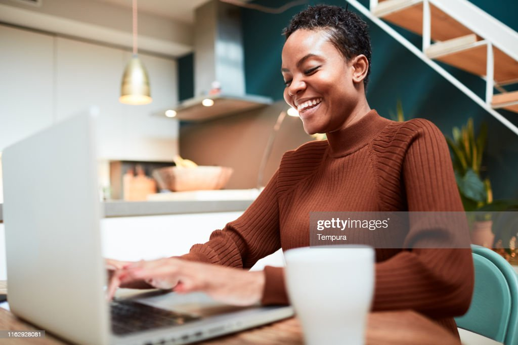 Woman working from home, messaging on-line with colleagues. : Stock Photo
