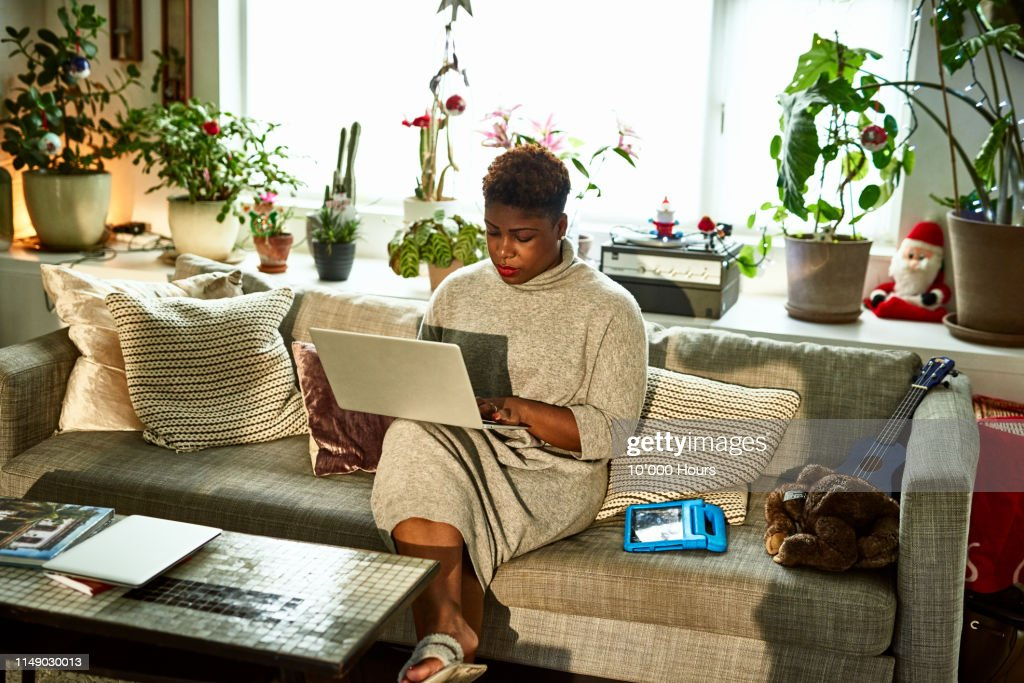 Woman working from home on sofa with laptop : Stock Photo