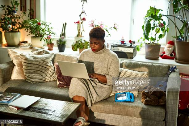 woman working from home on sofa with laptop - candid forum stock pictures, royalty-free photos & images