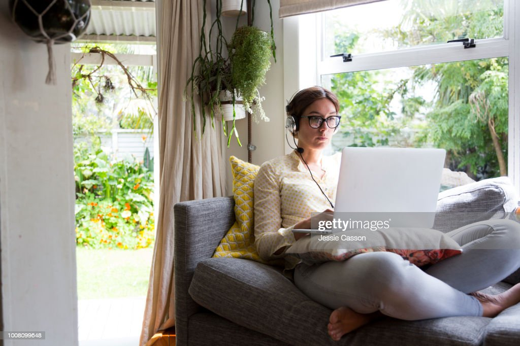 Woman working from home sitting on a sofa working on a laptop wearing a headset : Stockfoto
