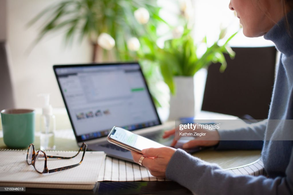 Woman working from home using laptop computer while reading text message on mobile phone : Stock Photo