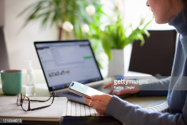 woman working from home using laptop computer while reading text message on mobile phone - laptop stock-fotos und bilder