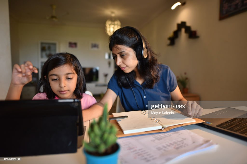 Woman working from home while daughter using digital tablet : Stock Photo