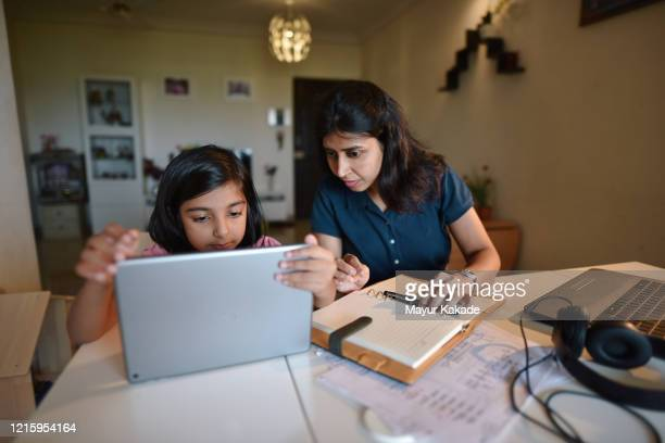 woman working from home while daughter using digital tablet - homeschool stock pictures, royalty-free photos & images