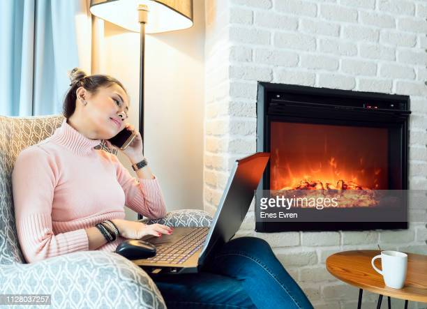 Woman working from home with laptop and talking on mobile phone