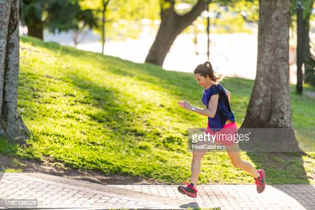 woman working hard running up a hill during a morning session in the park - sprinting stock pictures, royalty-free photos & images