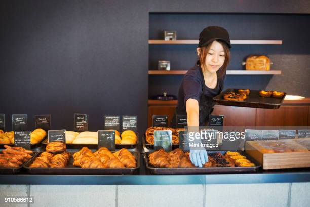 Woman working in a bakery, placing freshly baked croissants and cakes on large trays on a counter.
