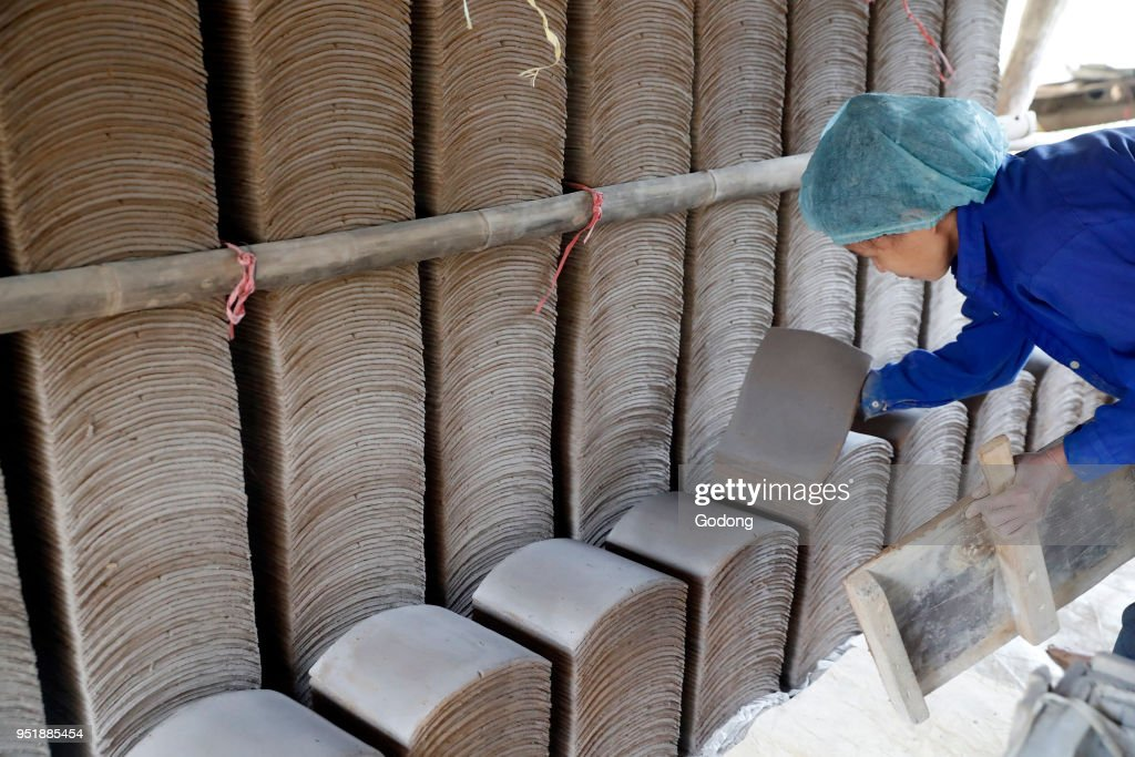 Woman working in a ceramic roofing tile factory. Pictures | Getty Images