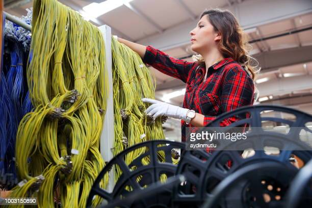 woman working in a factory - cable stock pictures, royalty-free photos & images