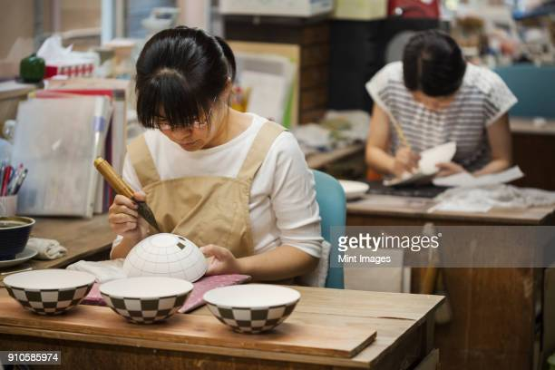 Woman working in a Japanese porcelain workshop, painting geometric pattern onto white bowls with paintbrush.