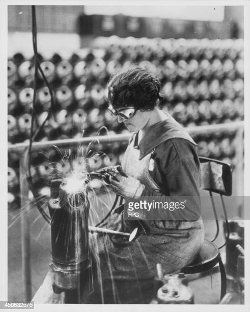 A woman working in a munitions factory during World War One aiding the war effort whilst the men are away USA circa 19141918