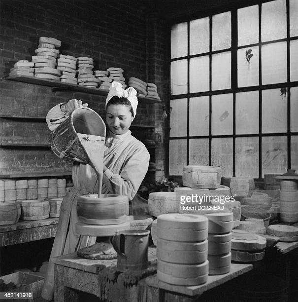 Woman working in a pottery workshop and pouring the clay into a mold in January 1951 in Limoges France