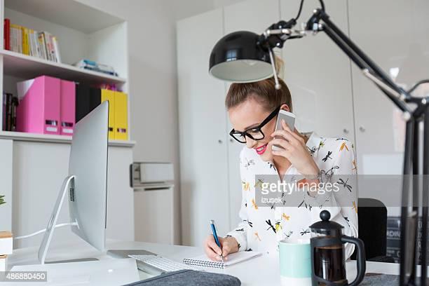 Femme travaillant dans le bureau, parler au téléphone intelligent