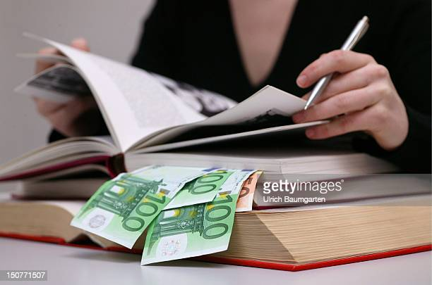 Woman working in books with Euro bank notes Symbol tuition fees free learning aids etc