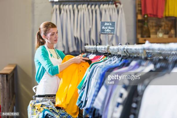 Woman working in clothing store hanging shirts on rack