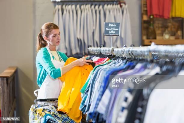 Frau arbeitet im Bekleidungsgeschäft hängende Hemden auf rack