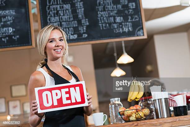 Woman working in coffee shop holding OPEN sign
