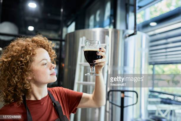 woman working in craft brewery checking quality of a beer - brewery stock pictures, royalty-free photos & images