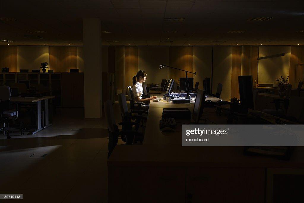 Woman Working in Dark Office : Stock Photo