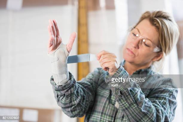 woman working in factory putting brace on wrist - brace stock pictures, royalty-free photos & images