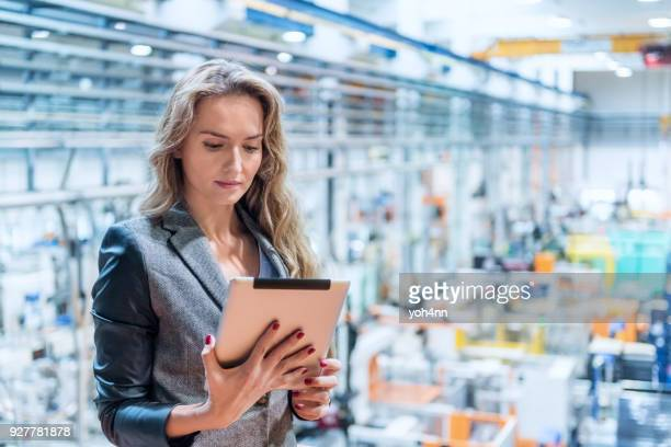 Woman working in factory & using tablet