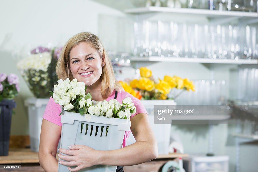 Woman working in flower shop carrying bin : Stockfoto