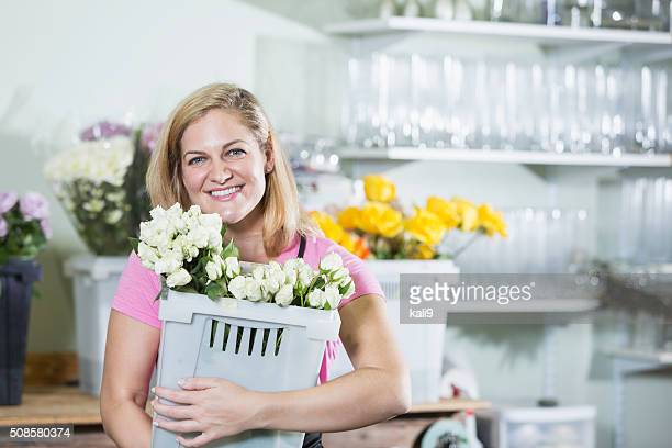 woman working in flower shop carrying bin - kali rose stock pictures, royalty-free photos & images