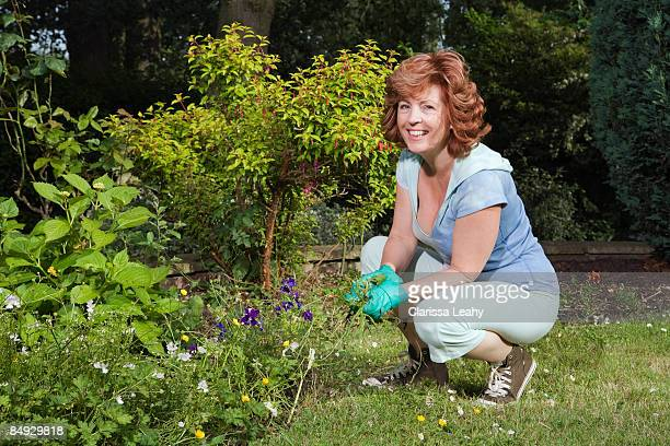 woman working in garden - kneeling stock pictures, royalty-free photos & images