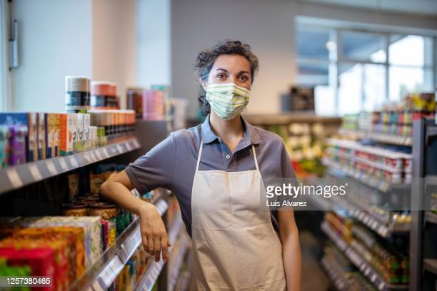 woman working in grocery shop during pandemic - essential services stock pictures, royalty-free photos & images