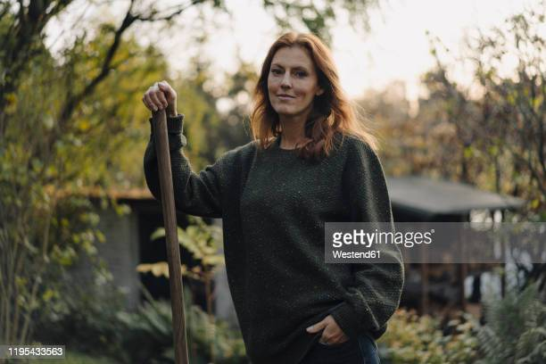 woman working in her garden, holding shovel - in den vierzigern stock-fotos und bilder