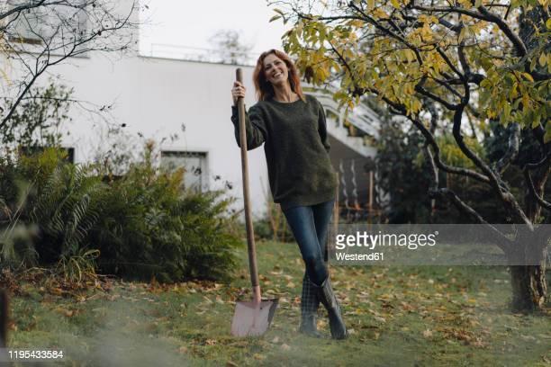 woman working in her garden, holding shovel - pelle photos et images de collection