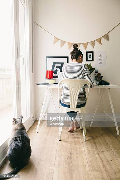 Woman working in home office with cat looking out of window
