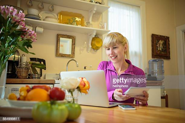 woman working in kitchen table reading instruction booklet and using laptop - heshphoto photos et images de collection