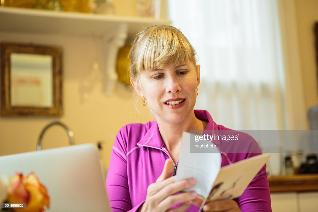 Woman working in kitchen table reading instruction booklet : Stock Photo
