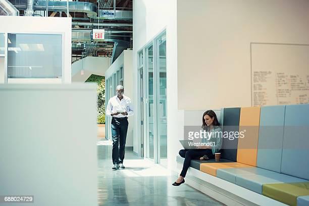 Woman working in lobby, colleague walking down corridor