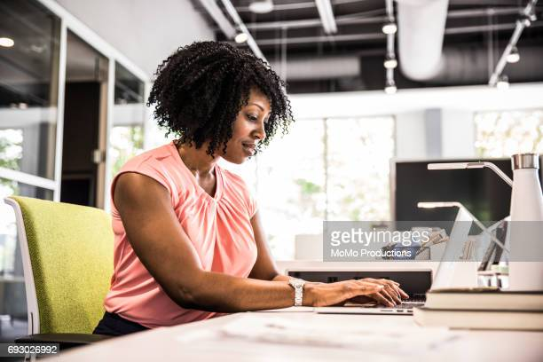 woman working in modern business office - leanincollection working women stock photos and pictures