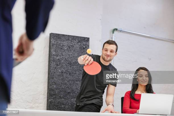 Woman working in office, while colleagues playing table tennis