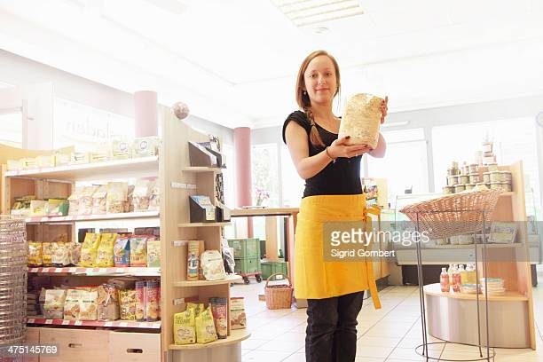 woman working in organic food market, holding packet of food - sigrid gombert stock pictures, royalty-free photos & images