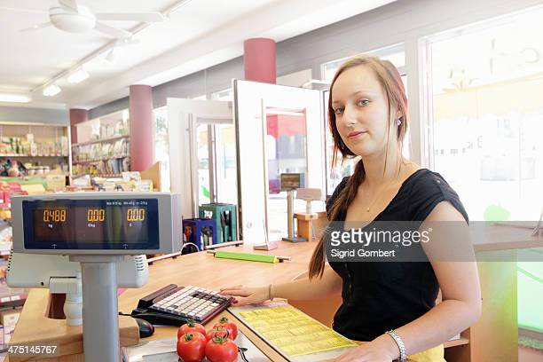 woman working in organic food market, serving at cash register - sigrid gombert stock pictures, royalty-free photos & images