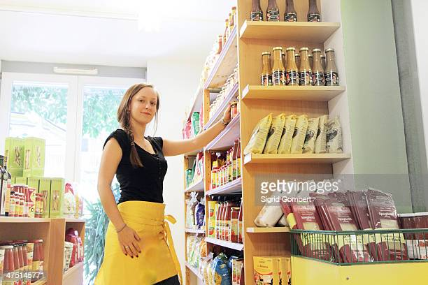 woman working in organic food market, stacking shelves - sigrid gombert stock pictures, royalty-free photos & images