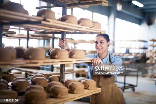 woman working in pottery studio. - pottery stock pictures, royalty-free photos & images