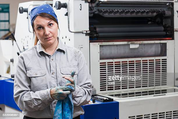 Woman working in printing plant wiping hands