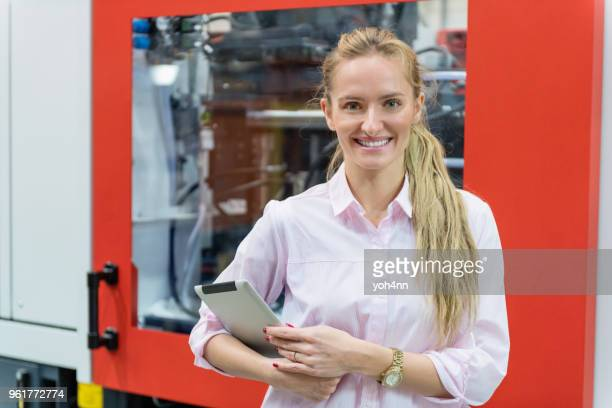 woman working in production line & smiling - mechatronics stock pictures, royalty-free photos & images